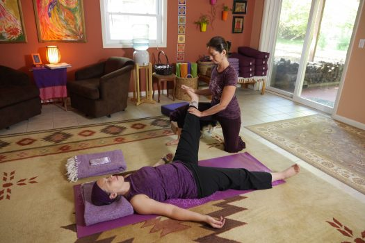 Yulia with a client holding her leg up during yoga therapy session