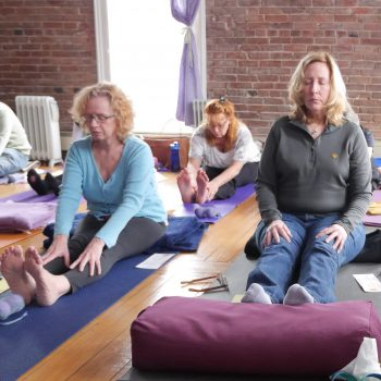 Student sitting on her yoga mat with eyes closed as others stretch around her